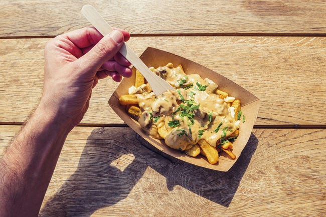 Man hold a fork to eat ench fries with mushrooms sauce on a wooden table, point of view shot. Belgium Fries Cupcakes Fork Fries Mushrooms POV Paper Cup Baked Cream Sauce Day Fast Food First Person View Food And Drink Freshness Holding Human Body Part Human Hand One Man Only People Potatoes Ready-to-eat Summer Tabel Unhealthy Eating Wooden