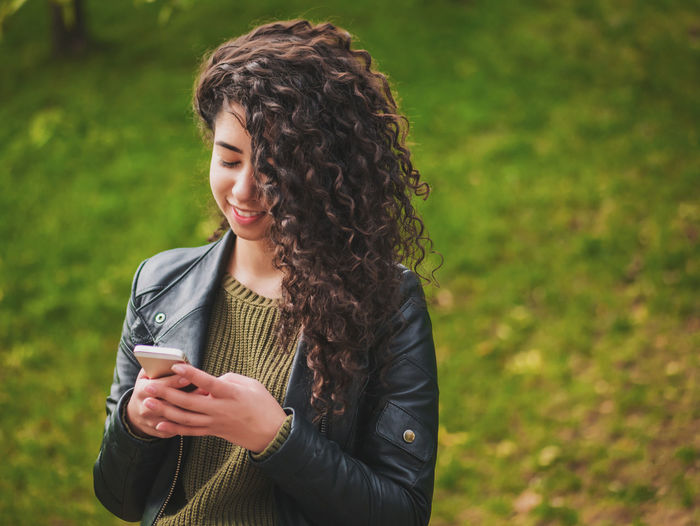 Autumn Beautiful Busy Fashion Green Color Lady Latin Mobile Phone Nature Student Typing On Keyboard Afrohair Curly Hair Cute Femininity Girl Hipster Hispanic Woman Leather Jacket Park Portrait Smart Phone Technology Woman Portrait Young Adult