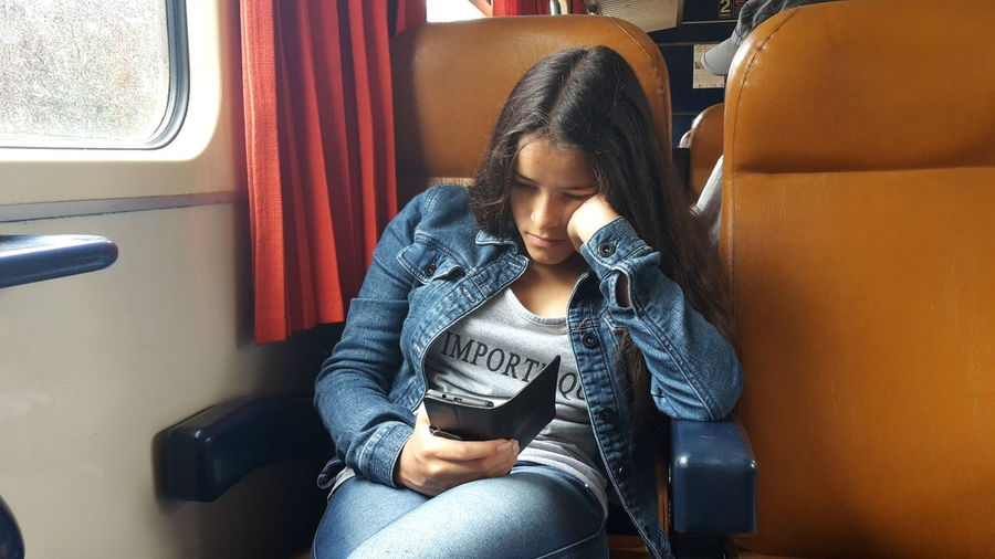 Girl using phone while sitting in train