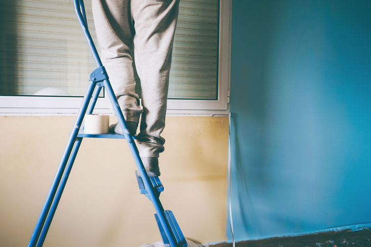Low section of man standing in front of ladder
