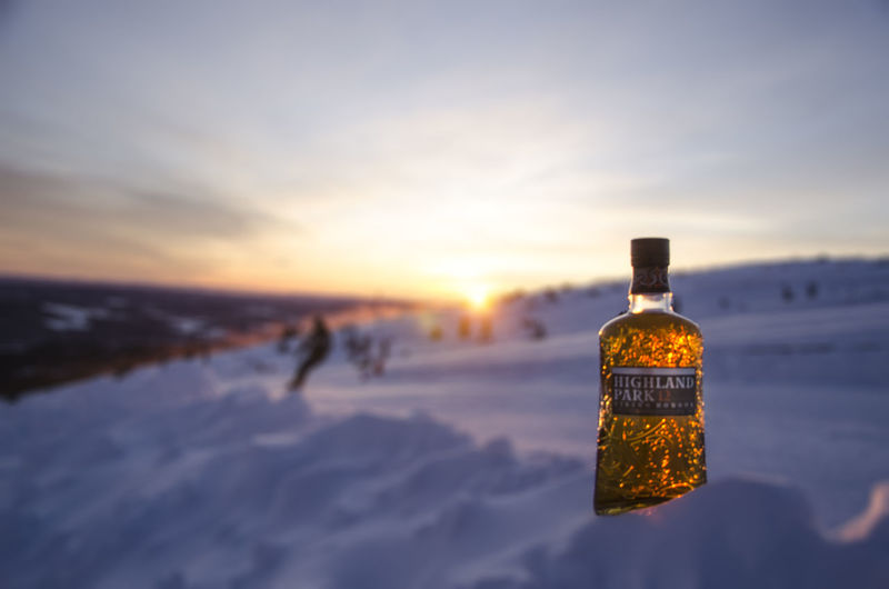 Close-up of snow covered bottle against sky during sunset