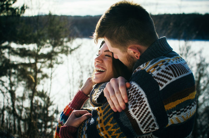 Joyful cute couple embraces. Young man in a sweater hugs a girl from behind background in winter. The concept of a successful relationship and happy moments Adults Only Cheerful Couple - Relationship Friendship Happiness Happy Moments Heterosexual Couple Hug Hugging Love Outdoors Romance Smiling Togetherness Two People Vacations Warm Clothing Winter Young Adult Young Couple Young Women