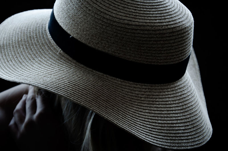 Close-up of person wearing hat against black background