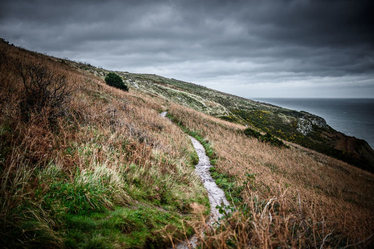 A road over the cliffs of Howth, near Dublin. Dublin Howth Ireland Scenic Travel Travel Photography Winter Beauty In Nature Cliff Cloud - Sky Day Grass Landscape Landscape_photography Nature No People Outdoors Scenic View Scenics Sea Sky Tourism Tranquil Scene Tranquility Travel Destinations