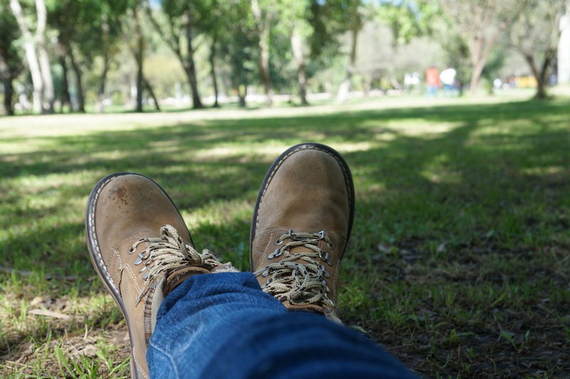 Low Section Of Man Wearing Shoes Resting On Grassy Field At Park