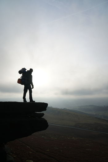 Silhouette man standing on edge of mountain against sky