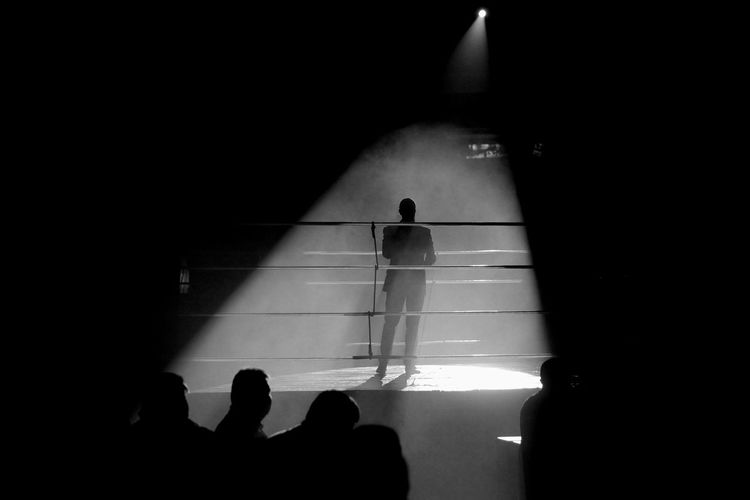 The event is in the language of the event the Boxing Ring Boxing Event Silhouette Silhouettes Boxing - Sport Dark Evening Illuminated Leisure Activity Lifestyles Light - Natural Phenomenon Men People Real People Ring Shadow Silhouette Sport Standing Sunlight Unrecognizable Person Walking