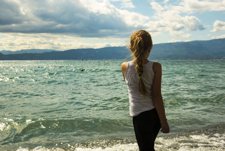 Rear view of girl looking at sea while standing on shore