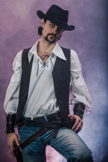 Handsome young man. This is an American cowboy. A vow to a white shirt, brown waistcoat and blue jeans. Black shoes on the feet. Carries a shtyapa, on a belt two pistols. The hair is of medium length; on the face is a beard and mustache. Authentic photo. Culture of America. Cowboy Wild West America American Gun National Lifestyles Lifestyle One Person Candid Authentic Three Quarter Length Front View Young Adult Young Men Casual Clothing Clothing Hat Real People Beard Facial Hair Social Issues Fashion Activity Standing