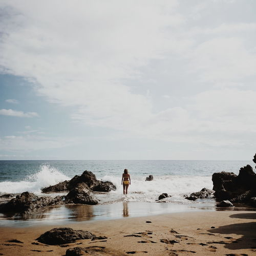 Rear View Of Young Woman Wearing Bikini Standing On Shore At Beach Against Sky