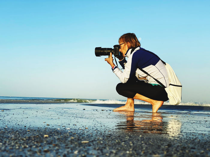 Man photographing in sea against clear sky