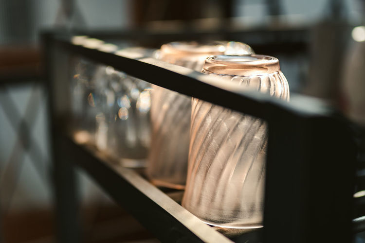 Close-up of drinking glass on shelf at restaurant