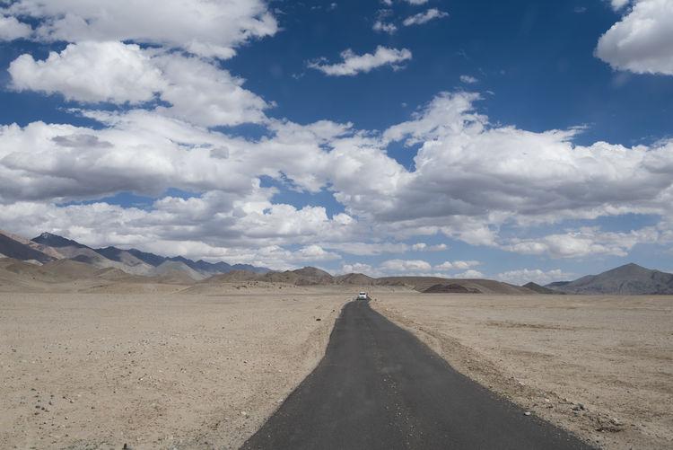 Road at desert against cloudy sky at ladakh