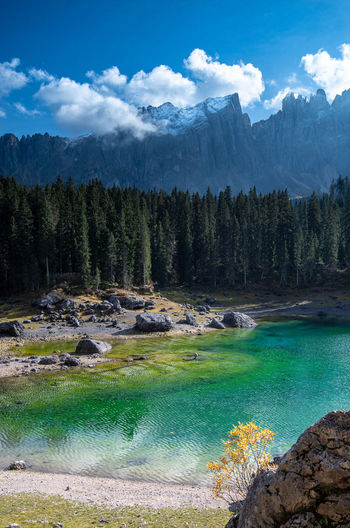 Scenic view of lake carezze  and mountains against sky in italy