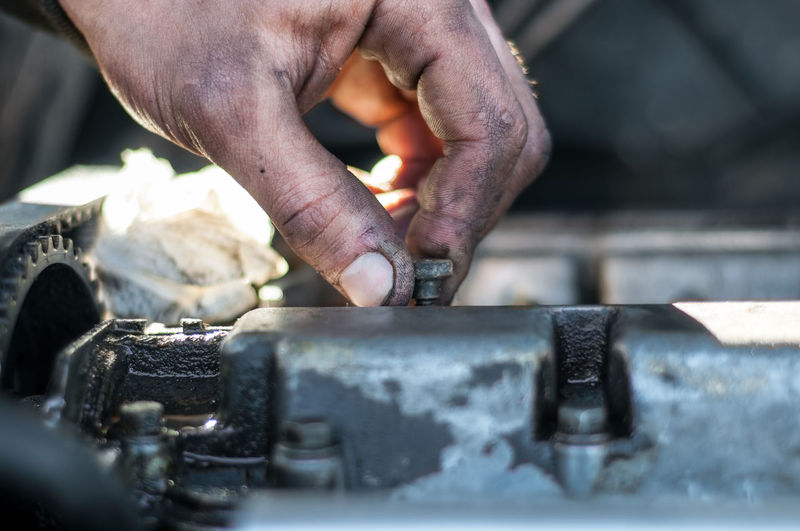 Cropped Hand Of Mechanic Working On Engine Of Car