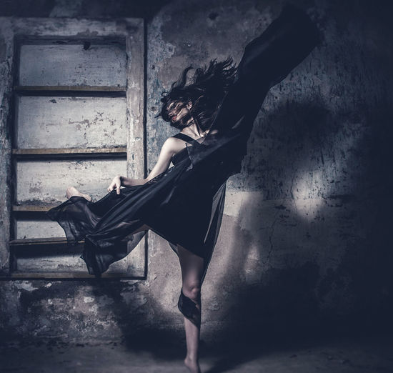 Young Woman Dancing Against Wall