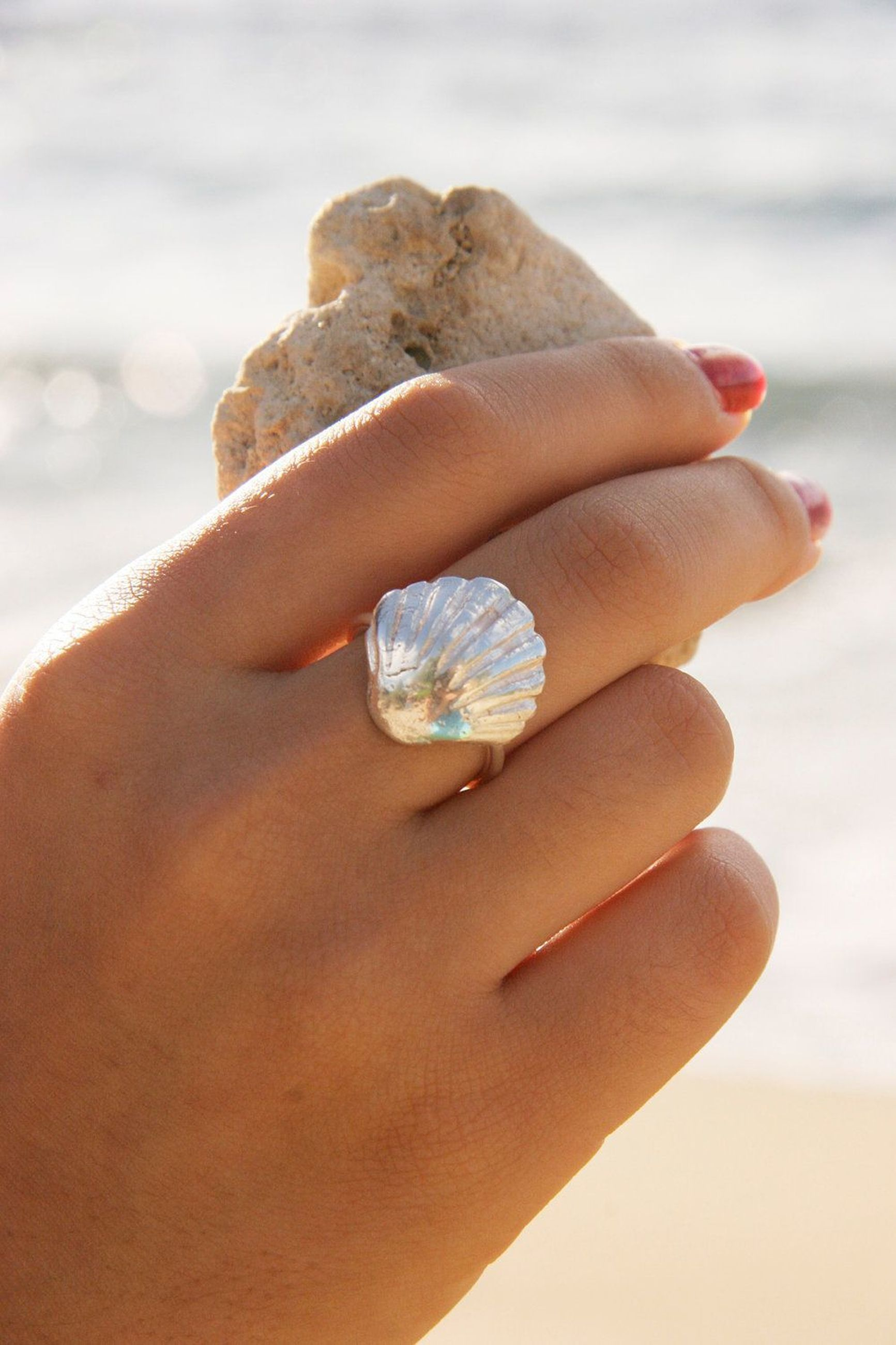 person, part of, human finger, holding, cropped, focus on foreground, close-up, personal perspective, unrecognizable person, sweet food, showing, lifestyles, seashell, leisure activity, beach, day, sand