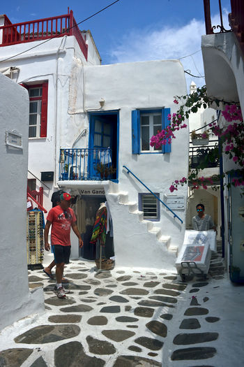 colored street view of Mykonos with man walking and a delivery man working. Building Exterior Architecture Built Structure Real People Building Full Length People Day Walking Lifestyles Women Nature Clothing Residential District Men City Leisure Activity Adult Outdoors Delivery Man Worker Tourist Tourism White Buildings Street Photography Street View Colored Windows Travel Mykonos,Greece Chora Urban Street City Town Holiday Greek Architecture Greece Summertime