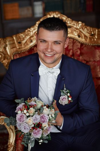 Portrait Of Bridegroom Sitting With Bouquet On Sofa