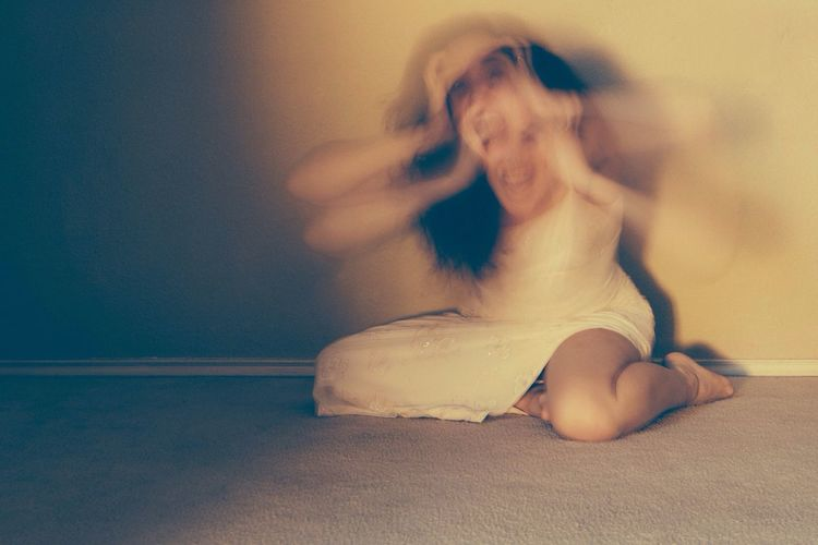Blurred Motion Of Woman Screaming With Holding Head Against Wall
