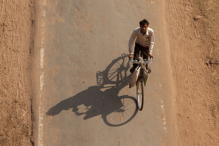 Unidentified man rides bicycle on the road in Orchha, India. ASIA Bicycle Bicycles Energy India Men Motion One Man Only Only Men Orchha People Ride Shadow Young Adult EyeEmNewHere EyeEmNewHere