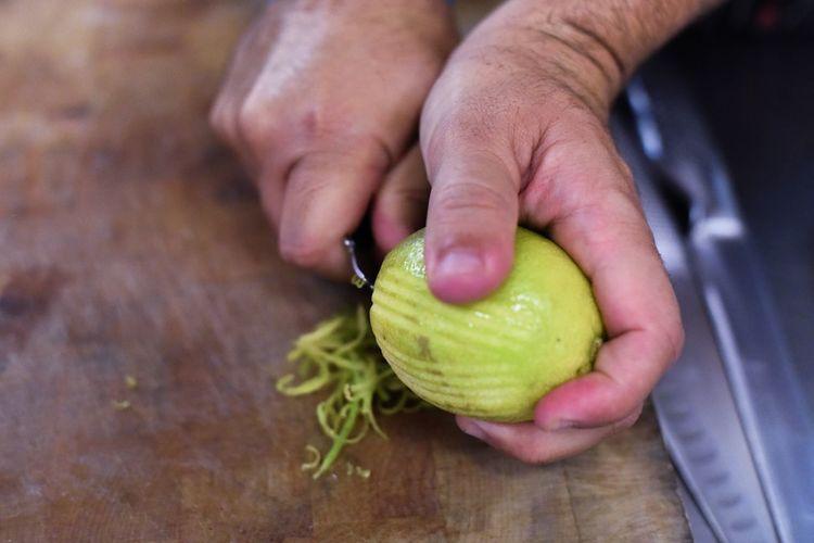 Cropped Hand Of Man Peeling Lemon On Cutting Board