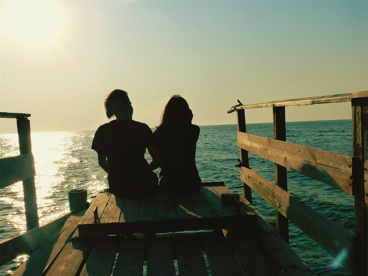 Couple - Relationship Two People Water Pier Silhouette Togetherness Adult Rear View Sea Wood - Material Women People Leisure Activity Men Standing Sunlight Love Day Adults Only Outdoors Jetty