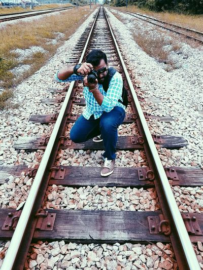 Rear view of boy photographing railroad tracks