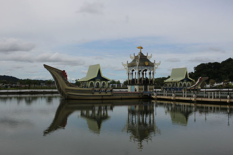 Reflection of temple in lake against cloudy sky
