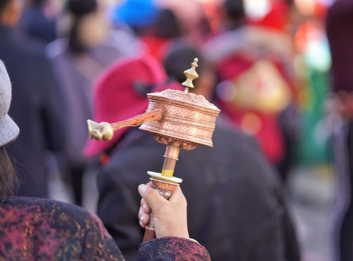 Rear View Of Woman Spinning Prayer Wheel Outdoors