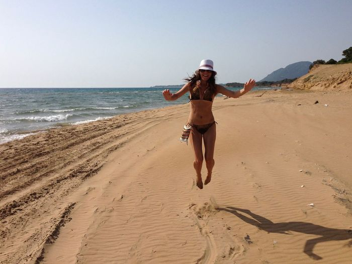 Full length of woman in bikini jumping at beach against clear sky on sunny day