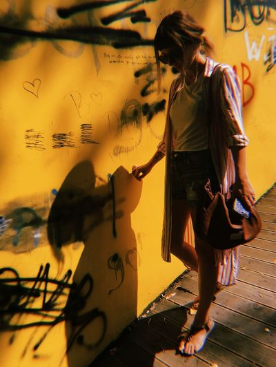 Graffiti One Person Casual Clothing Wall - Building Feature Real People Women Architecture Adult Built Structure Leisure Activity Shadow Lifestyles Full Length Fashion Day Creativity Standing Young Adult Hairstyle