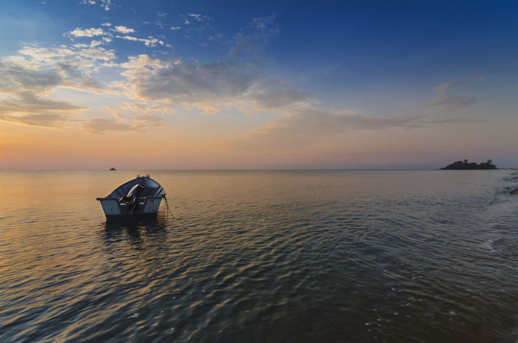 Lonely boat against blue sky during sunrise. Beauty Cloud Calmness Loneliness Lonely Seashore Transportation Beach Blue Sky Boat Countryside Seascape Sunrise Tranquil Scene Village Life
