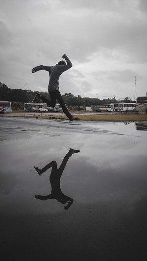 Man jumping in water against sky