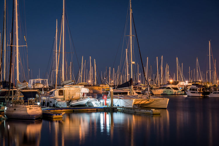 Sailboats moored in harbor at night
