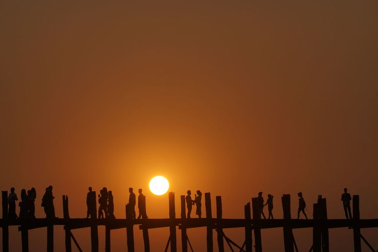 Silhouette people walking on pier at sunset
