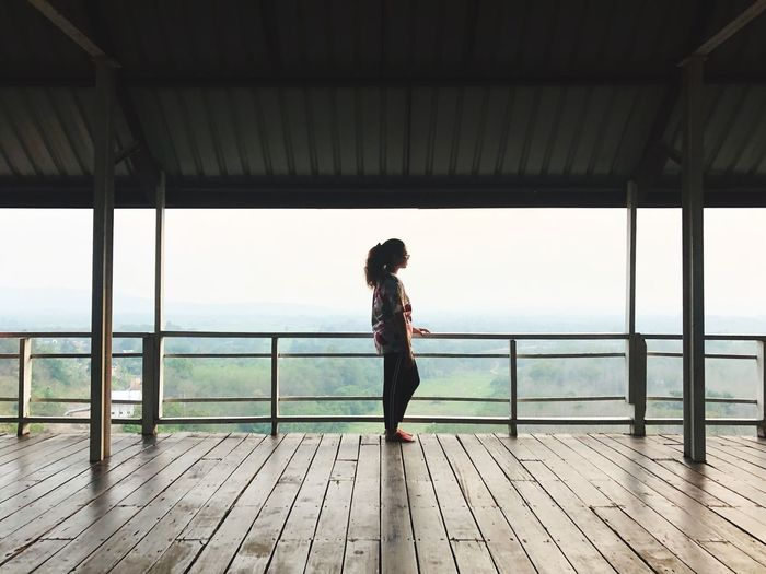 Wood - Material One Person Real People Full Length Lifestyles Leisure Activity Standing Railing Side View Women Horizon Looking At View Built Structure