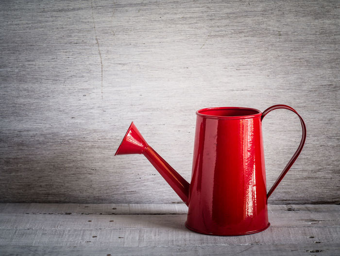 Accidents And Disasters Close-up Container Day Emergency Equipment Equipment Fire Extinguisher Flooring Hardwood Floor Indoors  Metal No People Pitcher - Jug Red Single Object Still Life Table Two Objects Wall - Building Feature Wood Wood - Material
