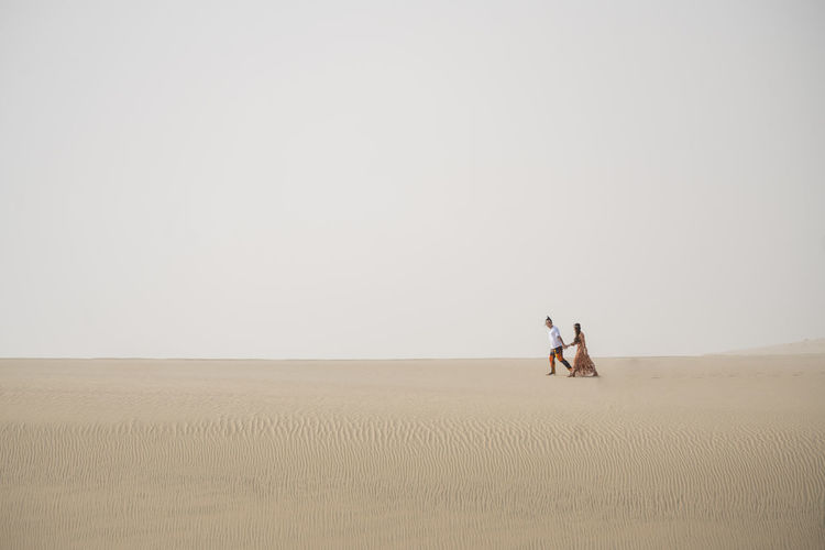 Long Shot of Couples walking in Desert Sand Dunes Copy Space Togetherness Two People Land Desert Sand Men Landscape Tranquility People Tranquil Scene Nature Women Adult Environment Climate Horizon Over Land Sand Dune Scenics - Nature Beauty In Nature Arid Climate Couple - Relationship Positive Emotion Outdoors Desert Love Space Empty Ijas Muhammed Photography