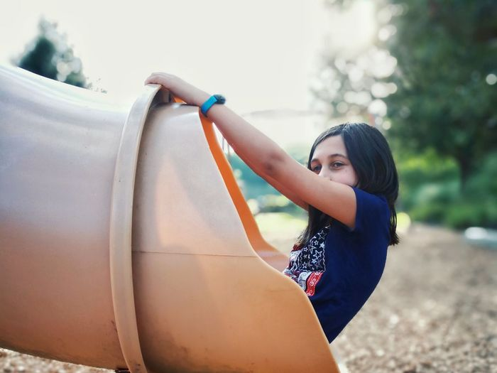 Girl playing in outdoor play equipment