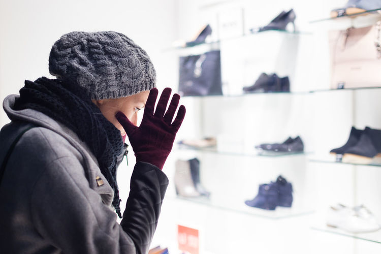 Side view of woman wearing knit hat standing in store