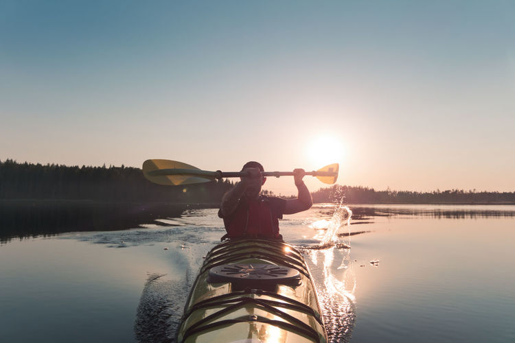 A man is swimming in a kayak. the sun shines behind him