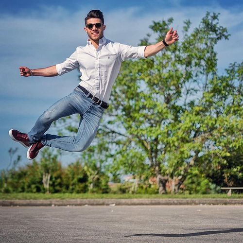 Young Man Jumping In City Against Sky