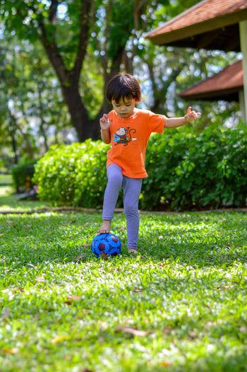 Full length of cute girl kicking ball on grass in park