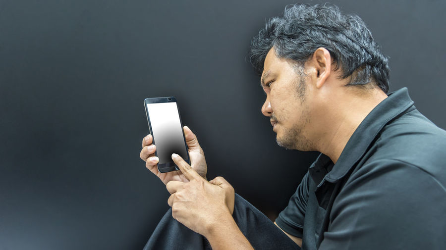 Low section of man using mobile phone