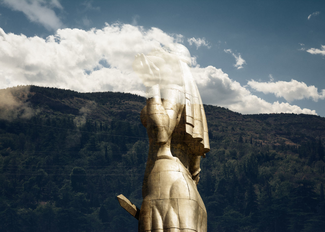 Double exposure image of statue and mountain