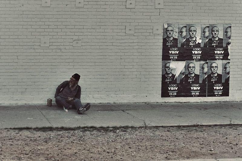 Man sitting on footpath against wall