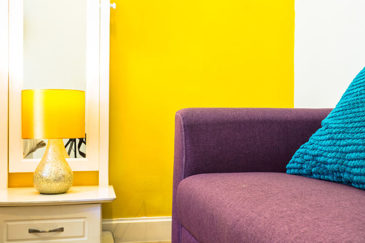 Close-up of sofa against yellow wall at home
