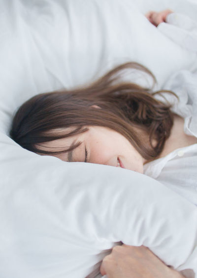 Portrait of a woman sleeping on bed