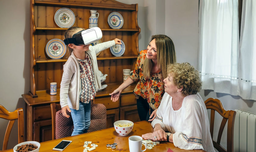 Girl with mother and grandmother wearing virtual reality simulator at home